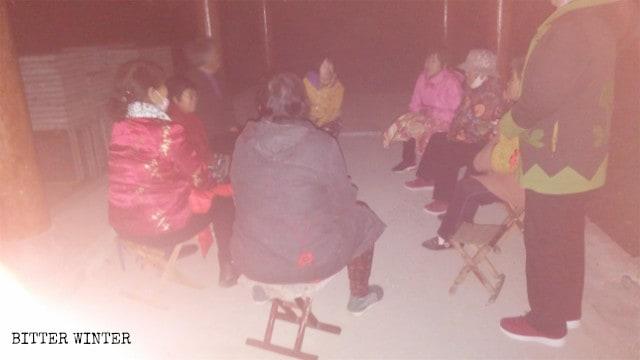 Cristianos de la tercera edad se reúnen en un quiosco fuera de la villa mientras está oscuro afuera.