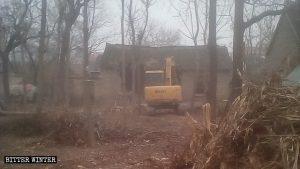 Una excavadora demuele la casa de una mujer anciana pobre.