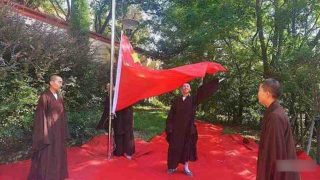 Monjes budistas asisten a una ceremonia de izamiento de la bandera