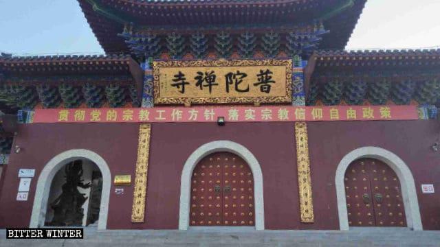Un irónico slogan propagandístico del PCCh cuelga frente al templo de Putuo