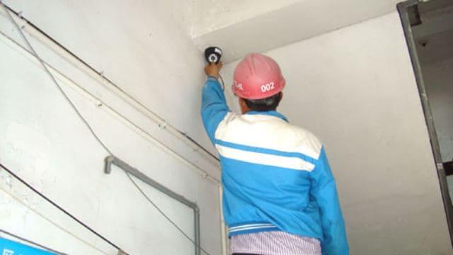 Un trabajador está instalando una cámara de vigilancia.