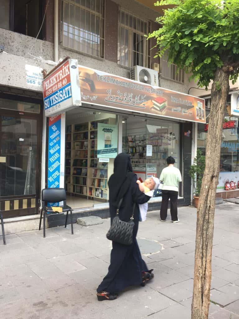 """Una """"viuda"""" uigur pasando por una librería uigur en Estambul."""