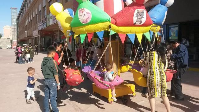 """Imágenes contrastantes de Sinkiang: niños jugando en el carrusel contra un trasfondo de """"milicias populares"""" practicando un simulacro en el mercado de Jotán."""