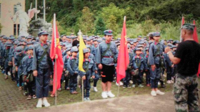 """Estudiantes con uniformes del Ejército Rojo llevan mochilas en las que están impresos un retrato del presidente Mao y la consigna """"Servir al pueblo""""."""