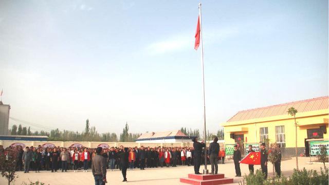 Las personas en una localidad de Xinjiang están organizadas para celebrar una ceremonia de izado de bandera