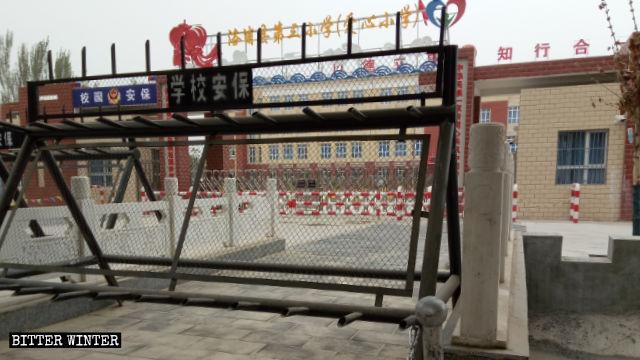 Una escuela primaria en el condado de Lop en Sinkiang acepta a los niños cuyos padres han sido encerrados en campamentos de transformación por medio de educación. La puerta de la escuela está estrictamente vigilada.