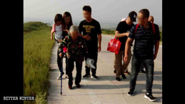 Una mujer mayor de pelo blanco tuvo que utilizar un bastón para llegar al lugar de peregrinación situado en la montaña.