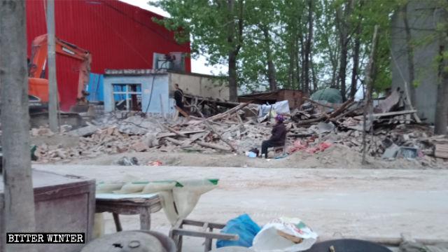Una mujer mayor sentada junto a las ruinas de su casa demolida en la ciudad de Zhumadian.