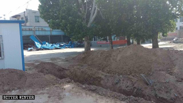 La excavadora cavó una gran zanja frente a la iglesia emplazada en la aldea de Renzhuang.