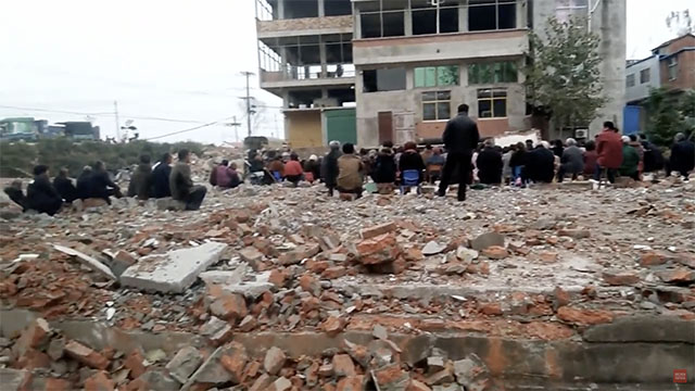Cristianos de un condado en Fuyang se reúnen en un campo de ruinas.