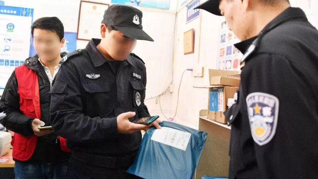 Oficiales de policía están examinando paquetes utilizando una aplicación móvil.