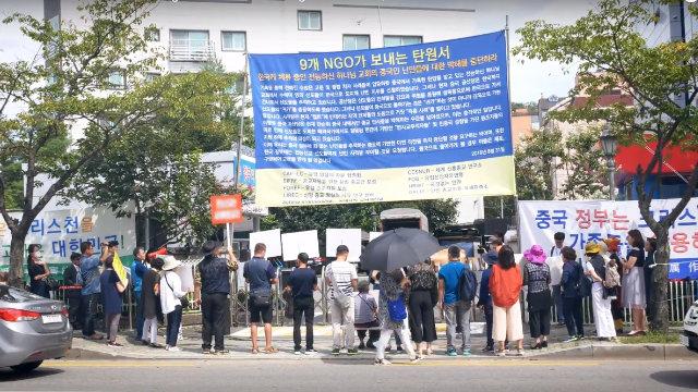 Organizados por el PCCh, familiares de miembros de la IDT y manifestantes profesionales protestan frente a la entrada de las instalaciones de la IDT en Seúl.
