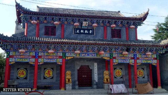 """En la actualidad, sobre la entrada de la sala ancestral de la familia Jin se ha colocado un letrero que dice: """"Auditorio cultural"""" y un retrato de Mao Zedong."""