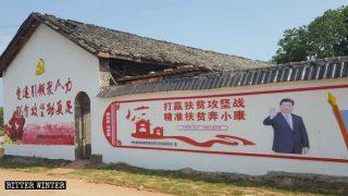 Carteles propagandísticos que promueven la campaña de alivio de la pobreza pegados en las paredes de casas rurales.