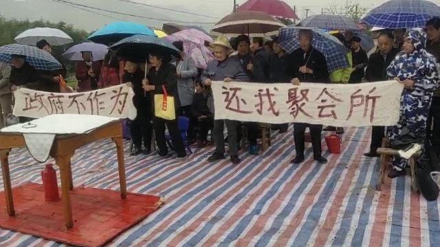 Los cristianos se reúnen en las ruinas de su lugar demolido, sosteniendo pancartas con mensajes dirigidos al Estado.