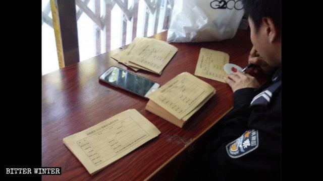 """Oficiales de policía están rellenando el """"Formulario de información personal de la base de datos de ADN"""" en un sitio de recolección de muestras de sangre."""