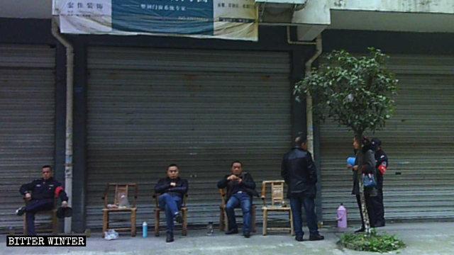 Miembros del personal de la oficina subdistrital vigilan la Iglesia de Qianxiang desde el otro lado de la calle.