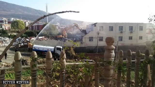 Una excavadora está demoliendo la Iglesia de Sigou.