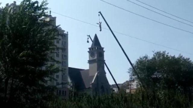 Una grúa está bajando la estatua de Jesús del campanario de la iglesia católica emplazada en la aldea de Linjiazhuang.
