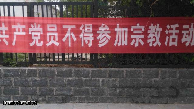 En una calle de Shangbali, un poblado bajo la jurisdicción de la ciudad de Huixian, en la provincia de Henán, se exhibe una pancarta en la cual se les prohíbe a los miembros del Partido participar en actividades religiosas.