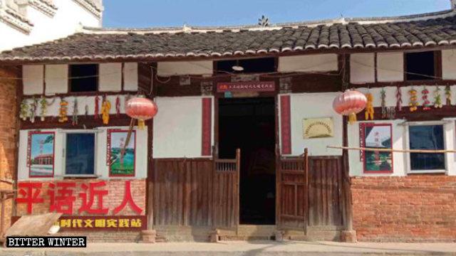 """Letrero con la leyenda: """"El idioma ping cercano al pueblo"""", colocado en la entrada de una """"estación de prácticas civilizatorias para una nueva era"""" emplazada en la aldea de Shangzhuang."""