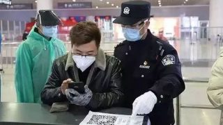 Los agentes de policía de un puesto de control situado en la estación ferroviaria este de Hangzhou les dan instrucciones a los pasajeros para que utilicen sus teléfonos móviles para escanear los códigos de salud.