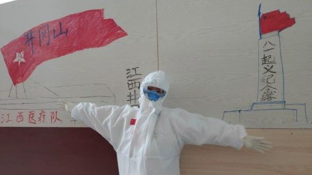 """Personal médico de la provincia de Jiangxi, enviado a brindar asistencia en un hospital modular de Wuhan, la ciudad donde se inició el virus, decorando una pared con imágenes de Jinggangshan a fin de mostrar su resolución de transmitir el """"espíritu Jinggangshan""""."""