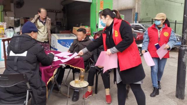 En el distrito de Liunan de la ciudad de Liuzhou, en la Región Autónoma Zhuang de Guangxi, miembros del personal comunitario le entregan a la gente folletos sobre prevención de la epidemia y religión.