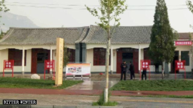 """El letrero que contenía el nombre del Templo de Yunzhong fue reemplazado por otro con la leyenda: """"Estación retransmisora del huerto de melocotones"""", acompañado de consignas que promueven los valores socialistas centrales."""