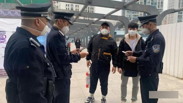 Oficiales de policía interrogan a los peatones durante la epidemia.