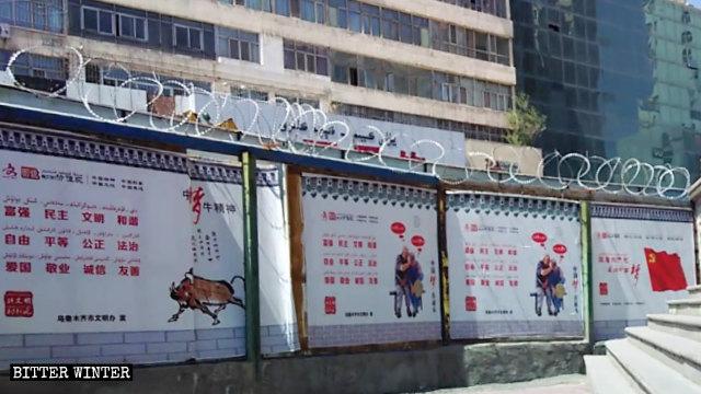 En un muro con alambre de púas se han colocado carteles propagandísticos que promueven el sueño chino del presidente Xi Jinping.