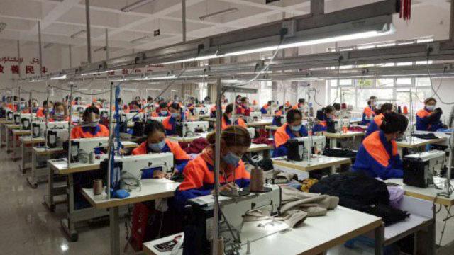 Mujeres uigures trabajando en una fábrica de ropa emplazada en el condado de Xinyuan de Sinkiang.