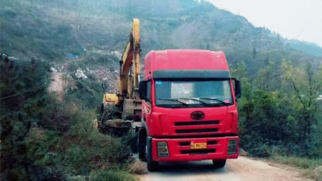 Una excavadora está subiendo una colina para demoler el templo.
