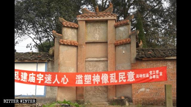 Una pancarta colocada por el Gobierno en la entrada de un templo advierte que los templos y las estatuas religiosas construidas sin aprobación son ilegales.