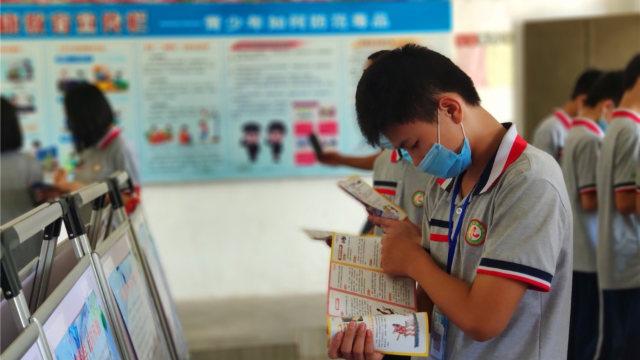 Un estudiante lee materiales anti xie jiao en el campus de una escuela emplazado en la ciudad de Enping de Cantón, en el mes de junio.