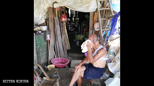 Un hombre de aproximadamente 80 años sentado fuera de su cobertizo.