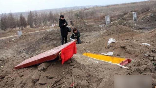 Una persona llora ante la tumba de un familiar exhumado.
