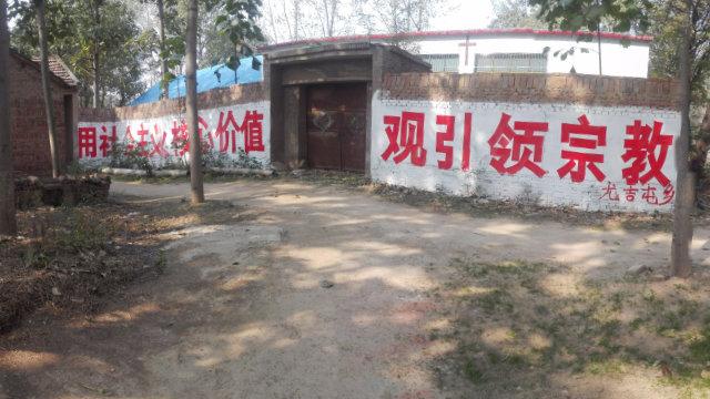 """Una pancarta colocada en la entrada de un lugar religioso dice lo siguiente: """"Utilicen los valores socialistas centrales para guiar la religión""""."""