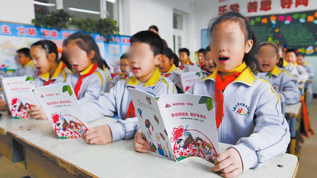 Estudiantes de una escuela primaria emplazada en Ürümqi, la capital de Sinkiang, están leyendo rimas infantiles en chino.